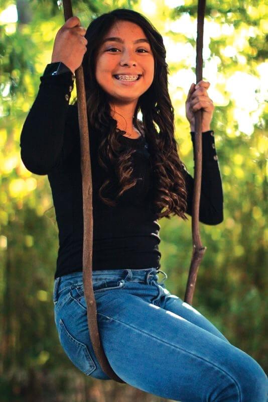 Image of teen girl swinging on a swing set