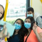 students riding the bus and taking selfies